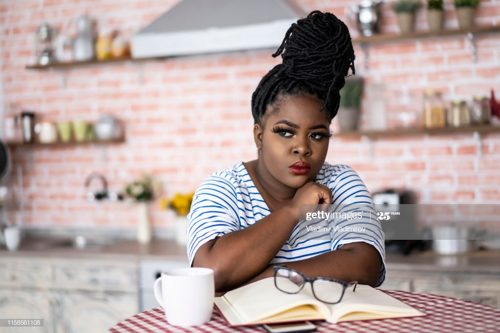 Young african woman sitting in kitchen at home.